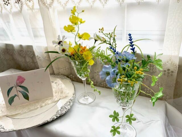 ガラスのグラスに飾られている黄色の花と水色の花